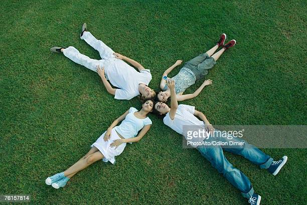 """""""group of young friends lying on grass, heads together"""" - x photos stock photos and pictures"""