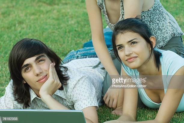 Group of young friends lying on grass using laptop