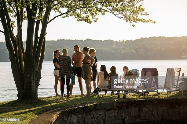 'Group of young friends partying at lakeside during sunset, Bavaria, Germany'