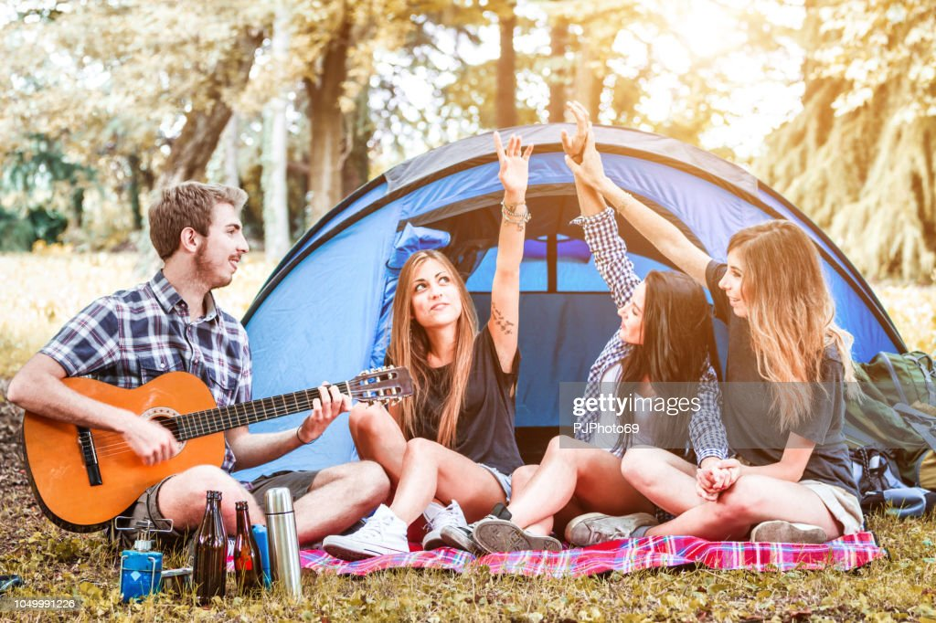 Group of young friends playing guitar and singing at camping : Foto stock