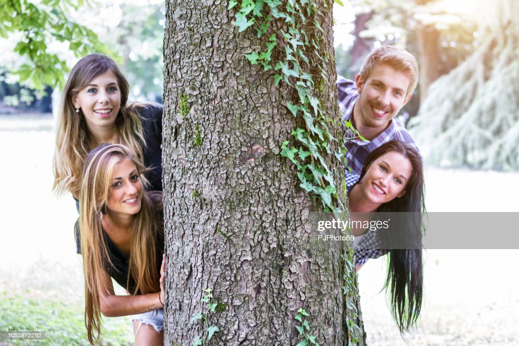 Group of young friends playing hide and seek outdoor : Foto stock