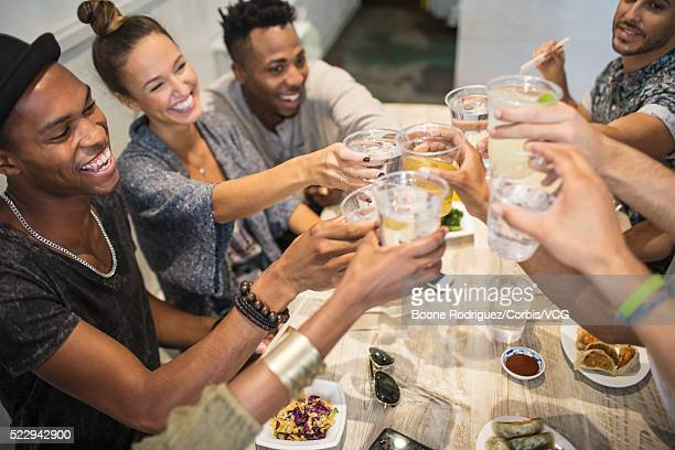 Group of young friends raising toast in restaurant