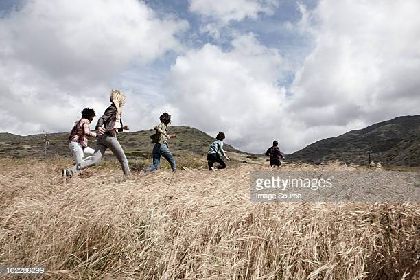 group of young friends running in field - following stock pictures, royalty-free photos & images
