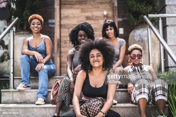 gruppo di giovani amici seduti su - afro americano foto e immagini stock