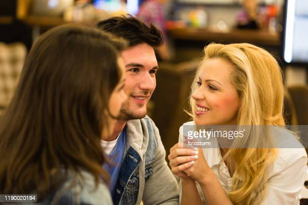 group of young friends smiling in a cafe - close to stock pictures, royalty-free photos & images