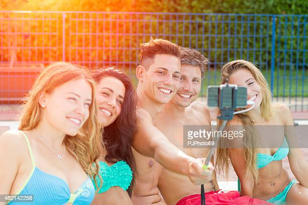 Group of young friends taking selfie at swimming pool