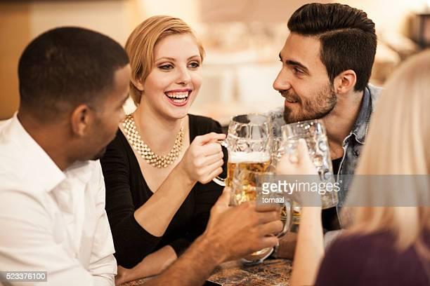 Groupe de jeunes amis parler dans un bar et d'un toast