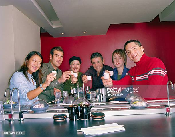 Group of young friends toasting in sushi restaurant, portrait