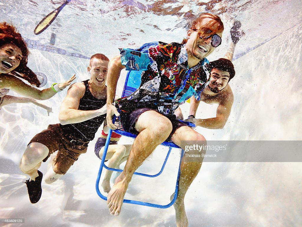 Group of young friends underwater in pool : Stock Photo
