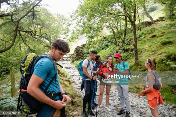 a group of young friends walking up a mountain path - backpacker stock pictures, royalty-free photos & images