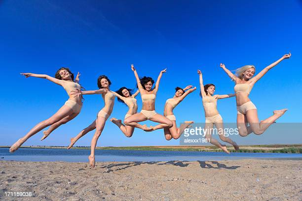 Group of young girls doing relaxation exercise outdoors at beach