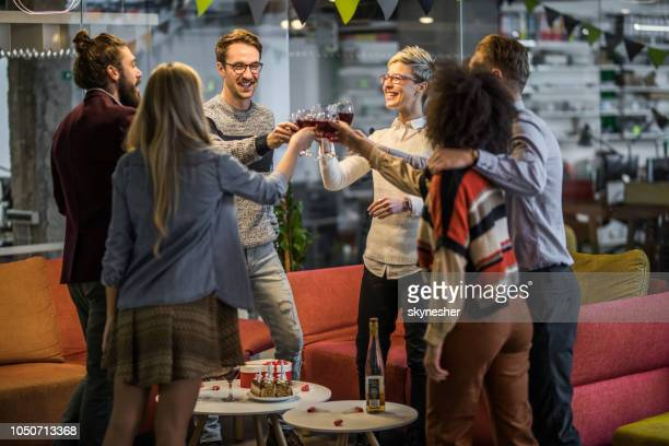group of young happy entrepreneurs toasting at office party. - work party stock pictures, royalty-free photos & images