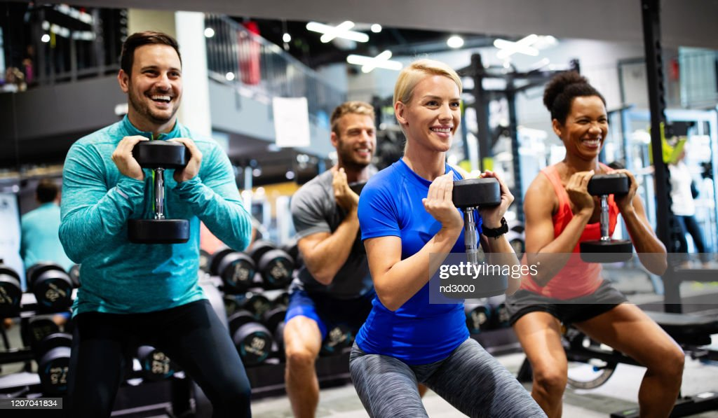 Group of young happy fit people doing exercises in gym : Stock Photo