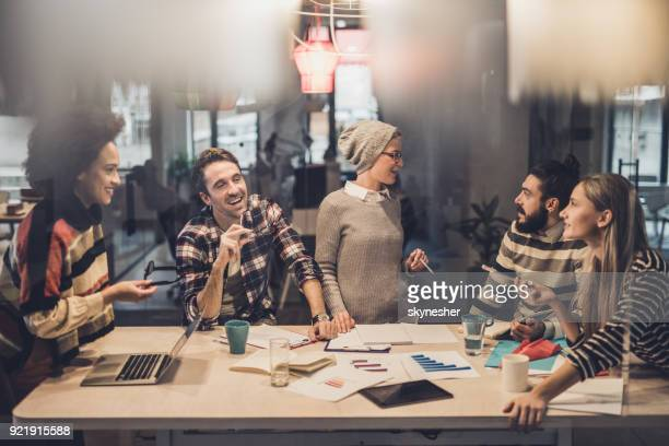 Group of young happy freelancers communicating on a meeting in the office.