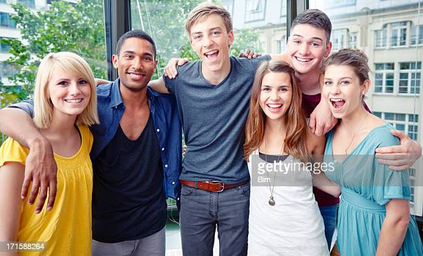 Group of Young Happy Smiling Students Standing Together Indoors