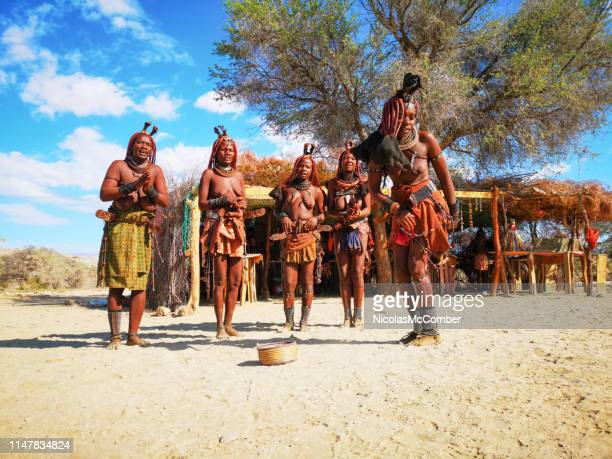 group of young himba women dancing in front of village market stall - himba foto e immagini stock