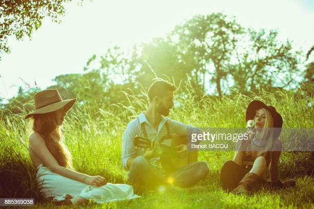 Group of young hipster sitting in the grass, playing guitar