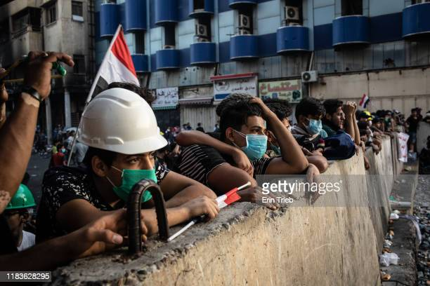 Group of young Iraqi protestors wait and watch behind a barricade for Iraqi security forces to react after the protestors launched stones with...