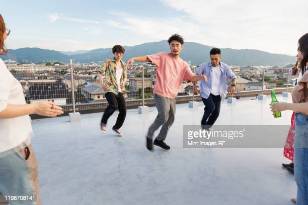group of young japanese men and women dancing on a rooftop in an urban setting. - ダンス ストックフォトと画像