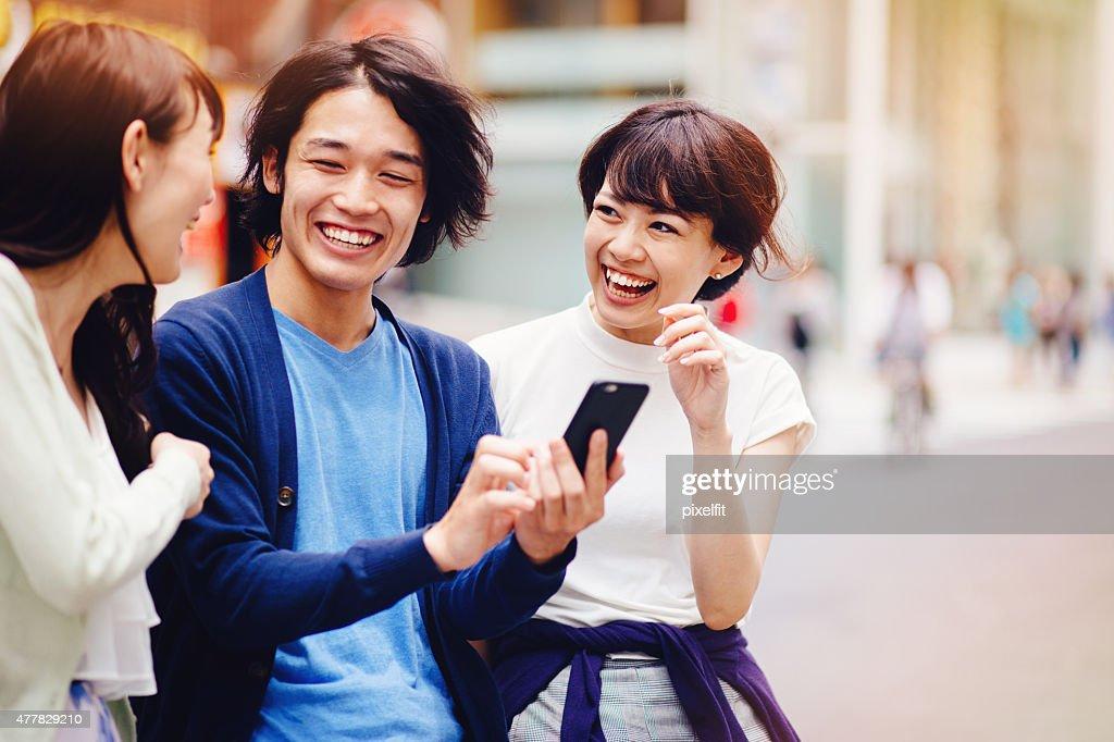 グループの若い日本人に、スマートフォン : ストックフォト