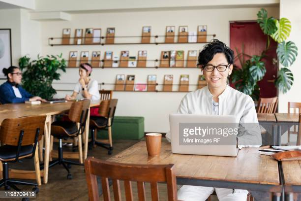group of young japanese professionals working on laptop computers in a co-working space. - 30 34歳 ストックフォトと画像