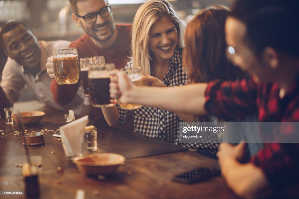 Group of young joyful friends having fun while toasting with beer in a pub. : Stock Photo