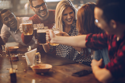 Group of young joyful friends having fun while toasting with beer in a pub. 955942630