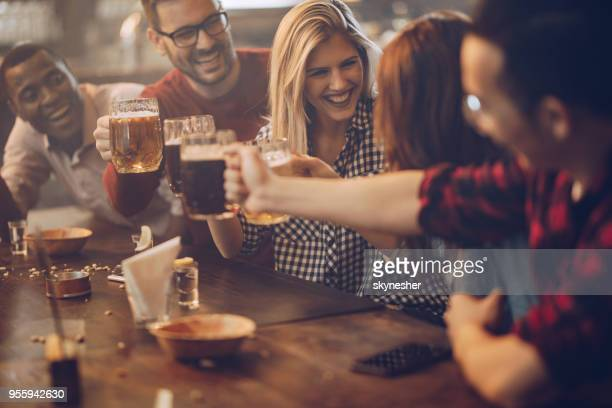 Group of young joyful friends having fun while toasting with beer in a pub.