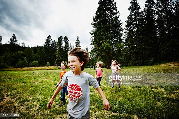 Group of young kids running race in grass field