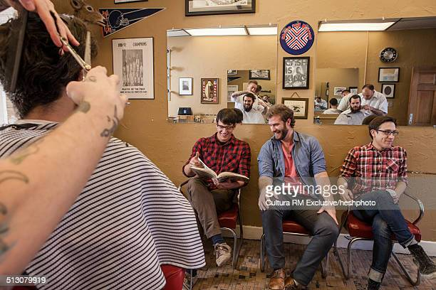 Group of young male adults friends waiting for haircuts in barbershop
