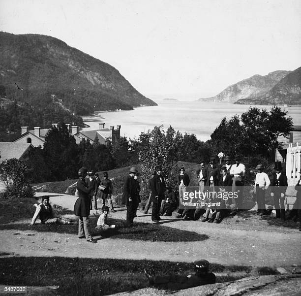 A group of young men and soldiers from the USMA relaxing on the banks of the Hudson River at West Point New York State