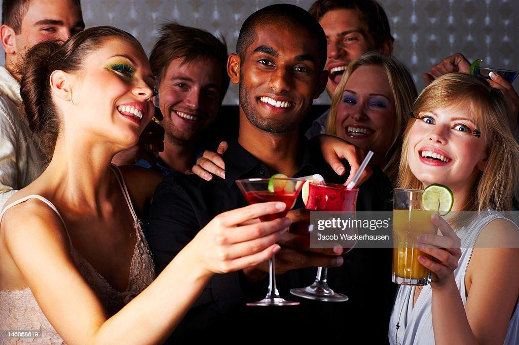 Groupe de jeunes hommes et femmes appréciant fête dans la discothèque