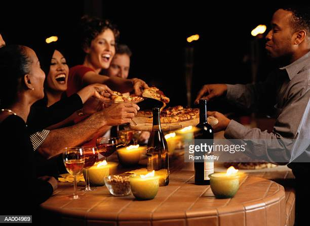 Group of young men and women in bar, sharing pizza