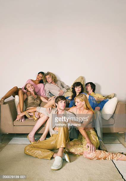 Group of young men and women relaxing on sofa
