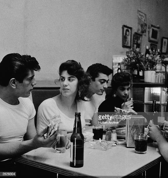 A group of young men and women sit together in a booth inside a pizzeria 1950s