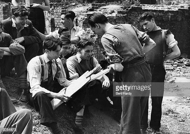 A group of young men choose bats from a selection of odd pieces of wood for a game of cricket in the bomb sites of London's East End Original...
