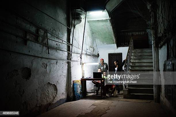 A group of young men gather around a laptop to watch videos in a cell phone repair shop in Old Havana From left to right are Julian Lara Andy Perez...