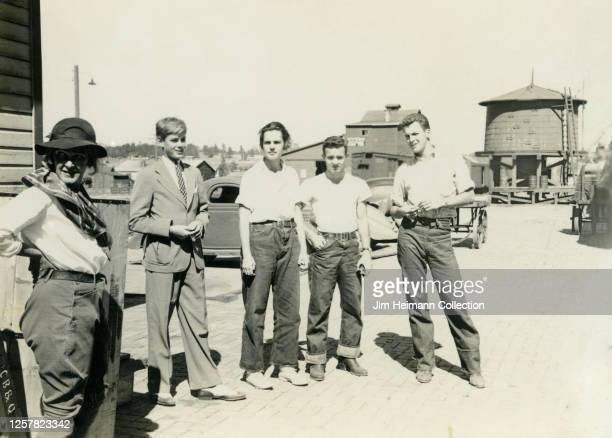 Group of young men in dungarees and white t-shirts stand around expectantly beside another young man in a suit and a woman in riding attire, circa...