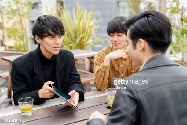 屋外で出会い、デジタルタブレットを見ている若い男性のグループ - ビジネスウェア ストックフォトと画像