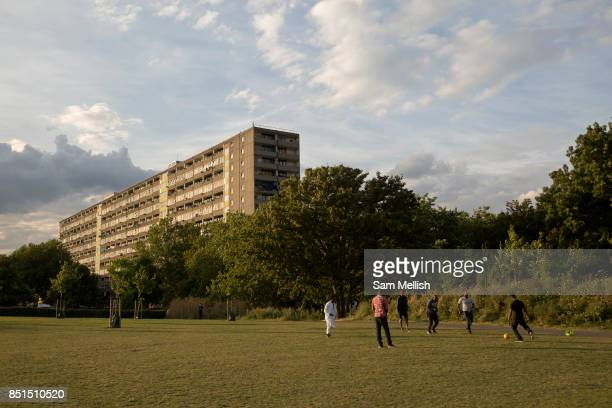 A group of young men playing football in Burgess Park overlooking the Aylesbury Estate a large housing estate located in Walworth on 5th August 2016...