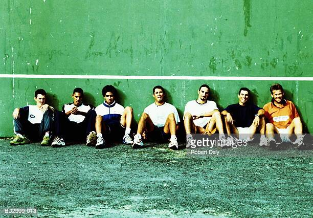 Group of young men sitting on sports court (cross-processed)