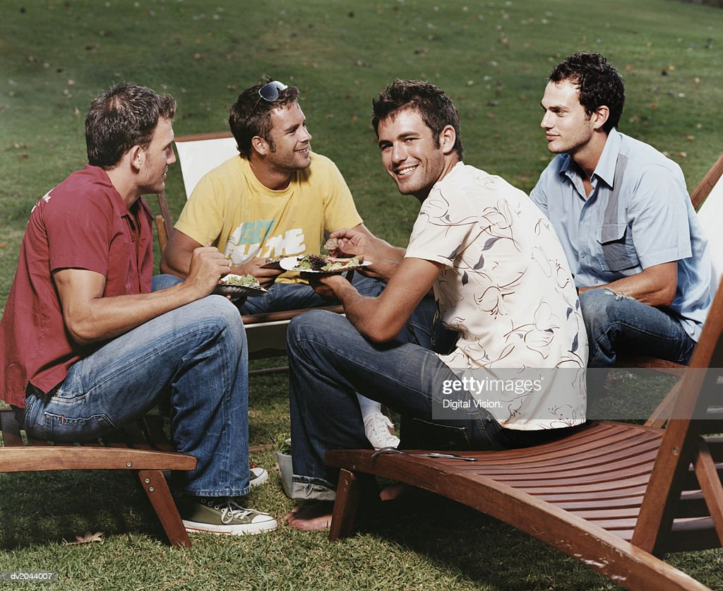 Group of Young Men Sitting on Sun Loungers Eating : Stock Photo