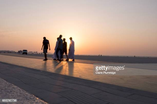 Group of young men walking on a purpose built walking/running track on a beach in Dubai at sunset
