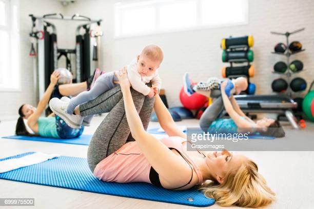 Gruppe von jungen Müttern und Babys Fitness trainieren im Fitnessraum. Gesunde Lebensweise.