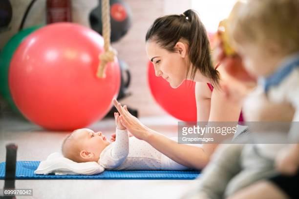 Groupe de jeunes mères et les bébés faire des exercices de remise en forme dans la salle de sport moderne. Mode de vie sain.