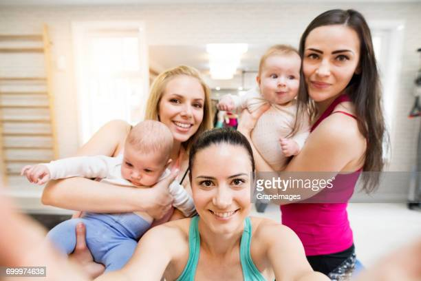 Group of young mothers and babies in modern gym with personal trainer taking selfie. Healthy lifestyle.