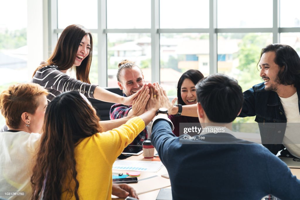 group of young multiethnic diverse people gesture hand high five, laughing and smiling together in brainstorm meeting at office. Casual business with startup teamwork community celebration concept. : Foto de stock