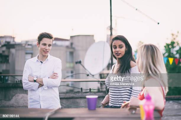 Group of young multi-ethnic people having fun on rooftop party