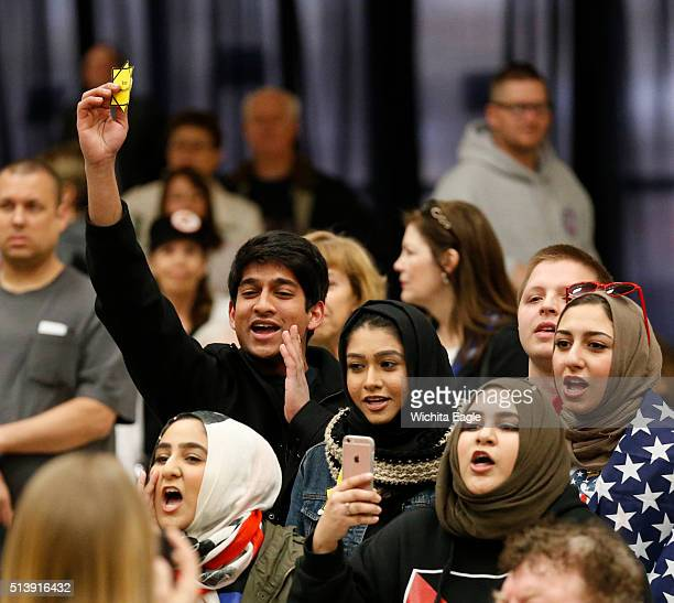 A group of young Muslims stage a small protest as Republican presidential candidate Donald Trump takes the stage for a campaign rally during the...