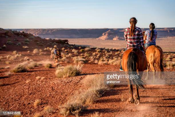 group of young navajo siblings riding their horses bareback through the vast desert in northern arizona near the monument valley tribal park on the navajo indian reservation at dusk - navajo culture stock pictures, royalty-free photos & images